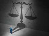 Homme devant une balance de justice en ombre portée
