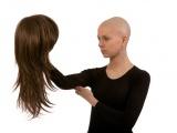 Femme sans cheveux qui tient une perruque